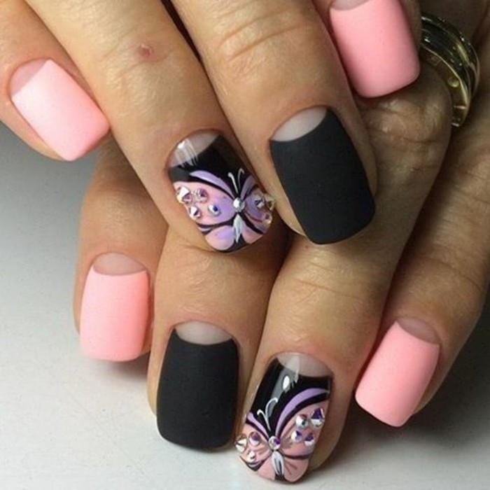 bling bling nails, two hands with nails painted in pale pink and black matte polish, ring fingers' nails painted with butterflies and decorated with rhinestones