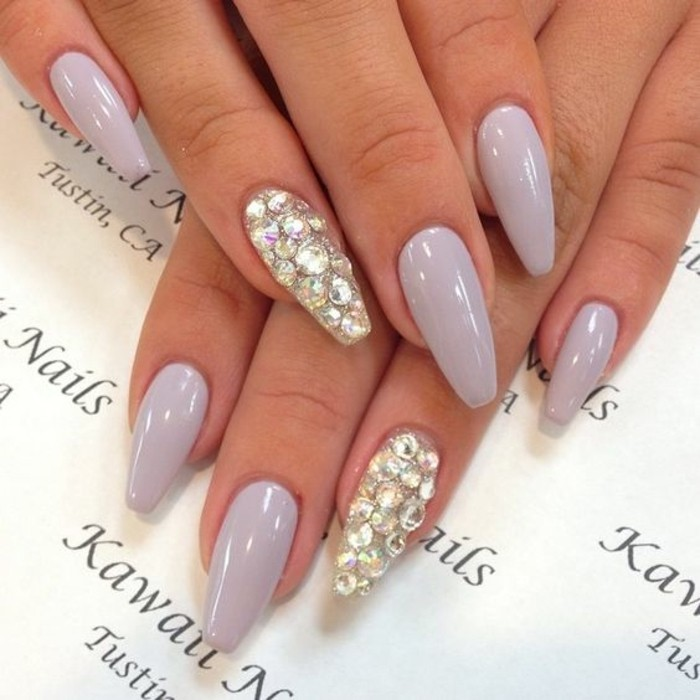 two hands with very pale lilac nail polish, ring fingers' nails entirely covered in rhinestones