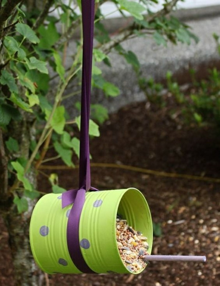 tin can projects, bird feeder made from tin can painted green, with purple polka dots, containing lots of different seeds, hanging on a purple ribbon