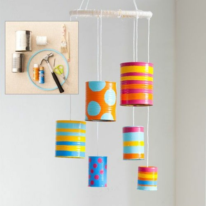 decoration made from six cans in different colors, decorated with paint in different colors, with shapes and stripes, hanging on white thread