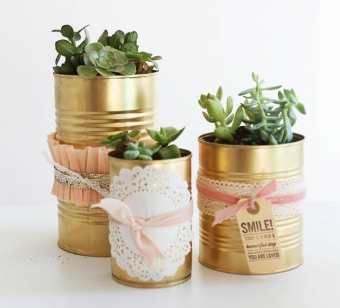 tin cans, three tin cans in different sizes, painted in gold paint and decorated with paper doilies, lace and pink ribbons, containing different succulents