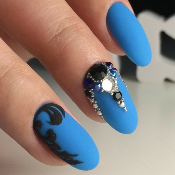 vivid blue matte nail polish, on three nails, one decorated with black sticker, one with black and white rhinestones