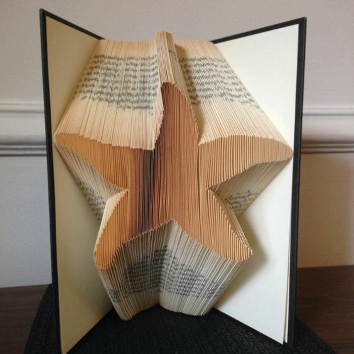 folded book art, opened book with black and white hard covers, containing starfish shape, made from folded pages