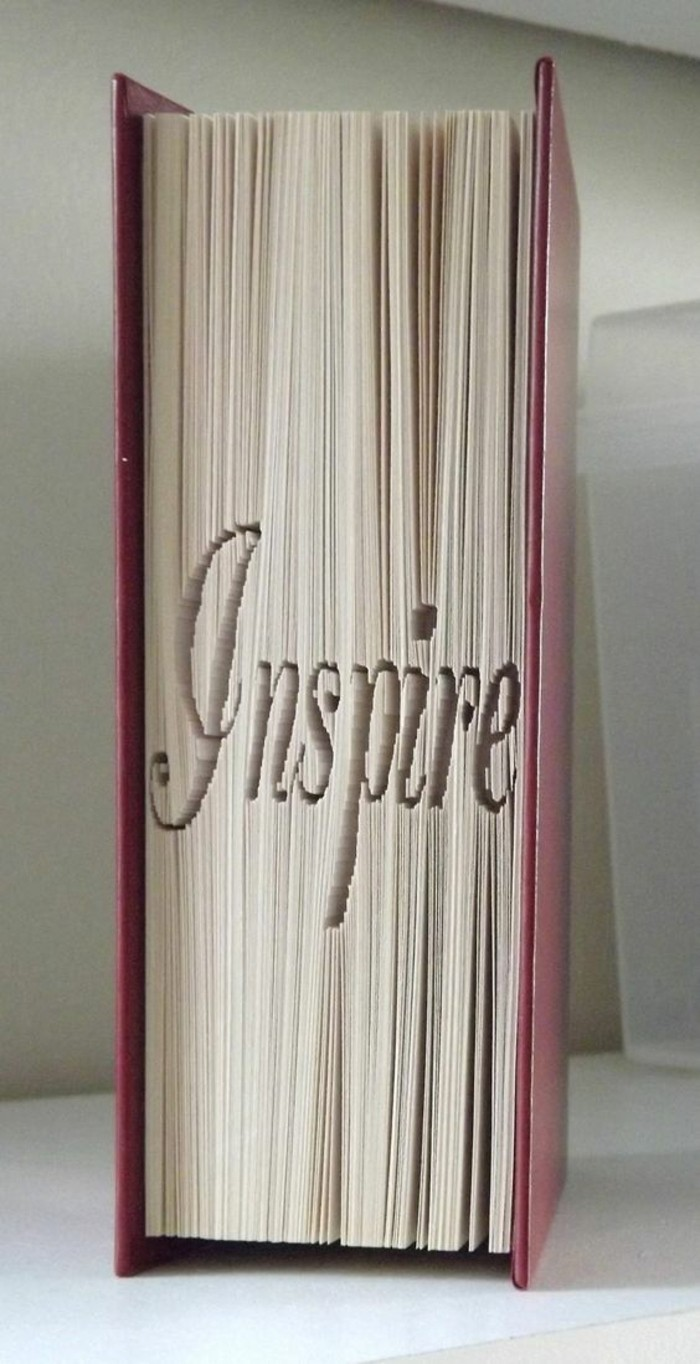 folded book art, closed book with hard purple covers, folded pages spelling the word inspire, in fancy writing