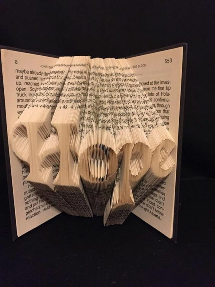 folded book patterns, the word hope, spelled in fancy writing, cerated by folded pages, inside a small opened book, with hard black covers