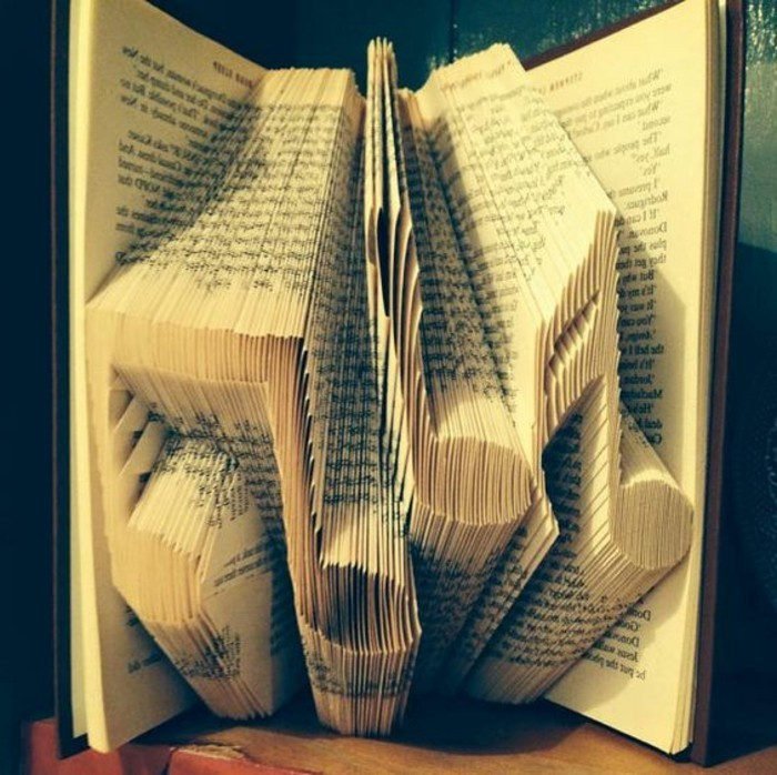 folded book art patterns, three musical notes, made from folded pages, inside an open book, with dark hard covers
