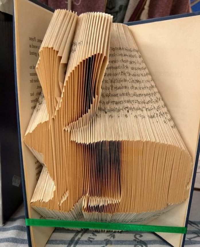 folded book art patterns, rabbit shape made from folded yellowy pages, inside an open book with dark blue hard covers, tied with a green ribbon