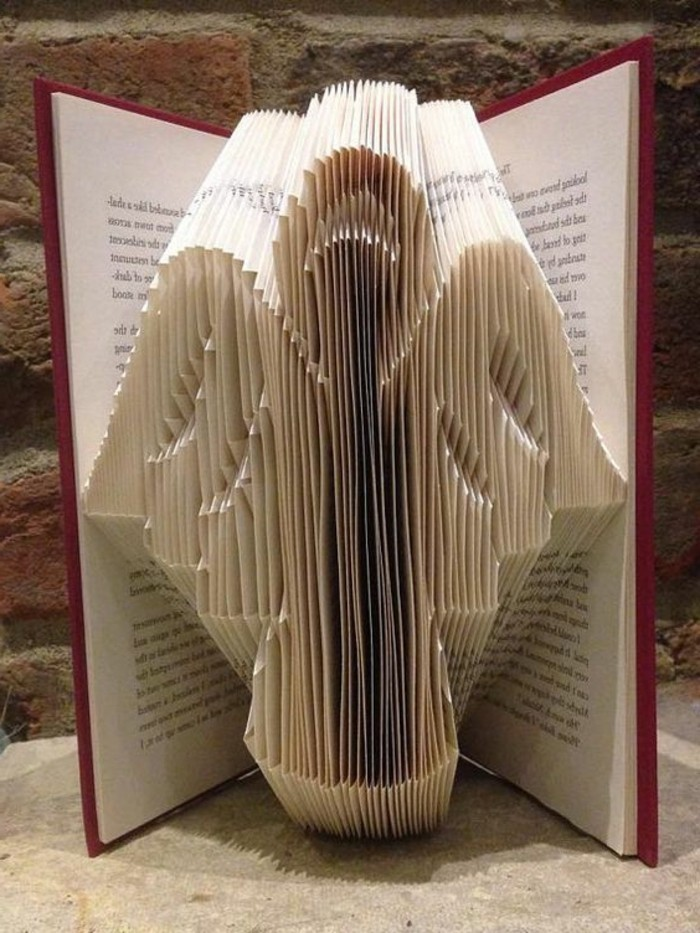 folded book patterns, simple angel shape, made from folded pages, inside an open book, with red hard covers