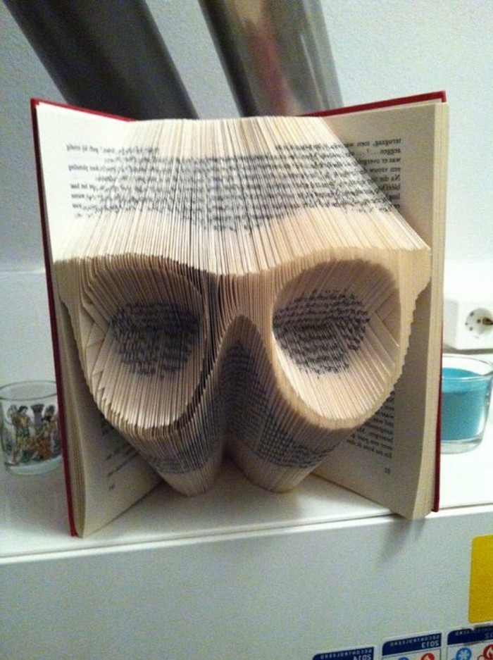 bookfolding, open book with red hard covers, containing eye glasses, made from folded pages