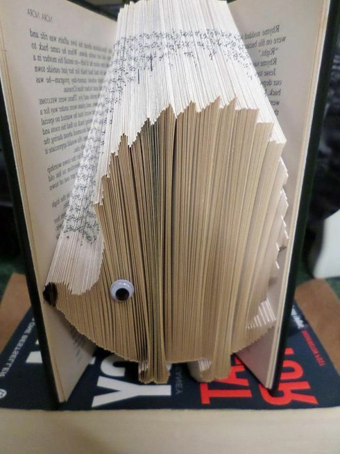 folded book patterns, book with black hard covers, opened to reveal a hedgehog shape, made from folded pages, decorated with black marker, and a stick-on googly eye
