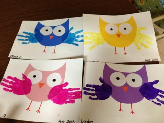 four pieces of white paper with owl collages in different colors, decorated with paper details and children's handprints