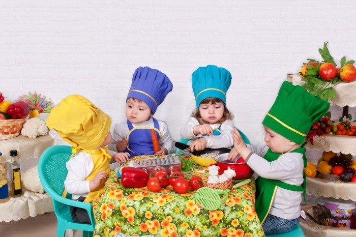 four toddlers wearing chef's hats and aprons in different colors, sitting on small plastic chairs around a table, with various cooking utensils and vegetables