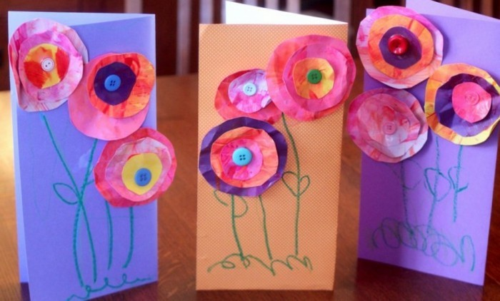 three cards made from violet and orange paper, decorated with paper flowers, made from crumpled hand-painted paper, decorated with buttons and crayon scribbles