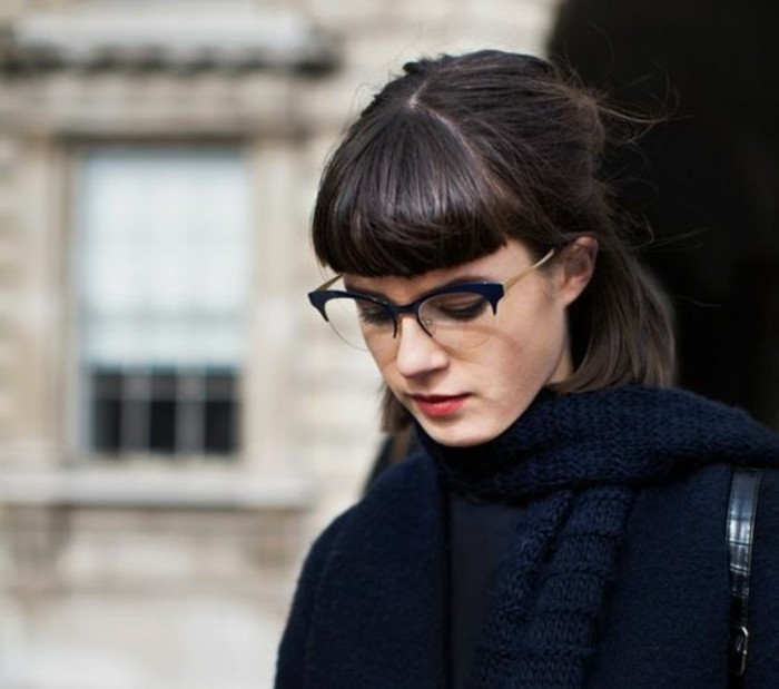 girl with dark brown, shoulder-length hair, tucked behind ear and tied at the back, with bangs and retro glasses