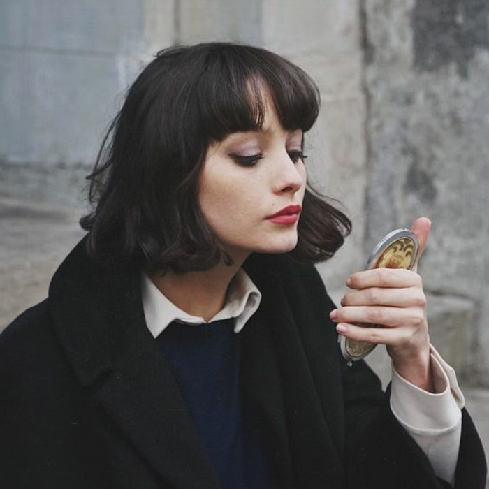young woman with chin-length, dark hair and bangs, wearing black woolen coat, and blue jumper over white shirt, holding compact mirror