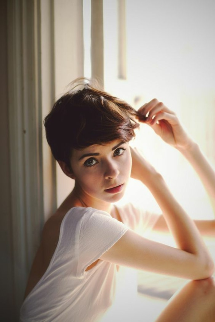 pixie cut, slim girl with big eyes, and very short wavy brown hair, longer bangs swept to one side on her forehead, wearing white open-back t-shirt