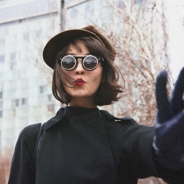 woman with wind-swept, chin-length brown hair and dark round sunglasses, wearing brown cap and black coat, making the peace sign, with one gloved hand