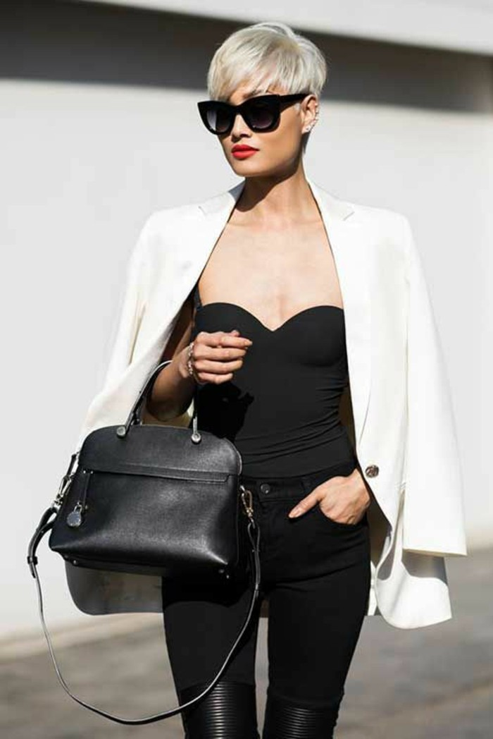 slim woman with short platinum blonde haircut, wearing black sunglasses and bright red lipstick, with black strapless top and trousers