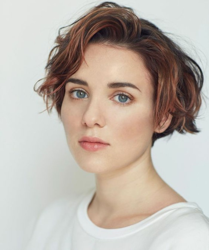hairstyles for short hair, young woman with big blue eyes, with short wavy hair with pink highlights, wearing white t-shirt and natural-looking make up