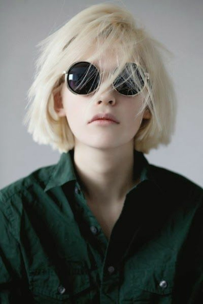 cute hairstyles, young woman with messy platinum blond bob, several strands on her face, wearing black round sunglasses and dark green shirt