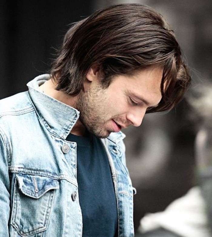 smiling man looking down in profile, with stubble beard and mustache, wearing light denim jacket and dark blue t-shirt, straight chin-length hair