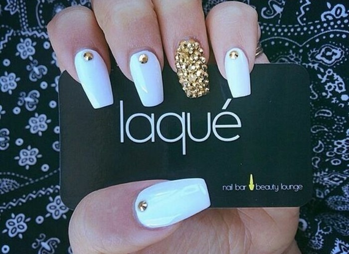 hand with long square nails, four painted white and decorated with a single golden rhinestone, one entirely covered in gold rhinestones, holding black business card
