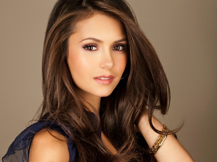 nina dobrev, with wavy long brown hair, dark brown eyes, delicate natural make up, wearing blue short-sleeved blouse and gold bangle