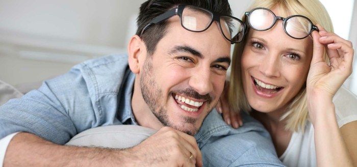 hazel eye color, laughing man with dark hair, short beard and mustache, wearing pale denim shirt, with glasses over his head, next to a laughing blonde woman with white top, also with glasses on her head