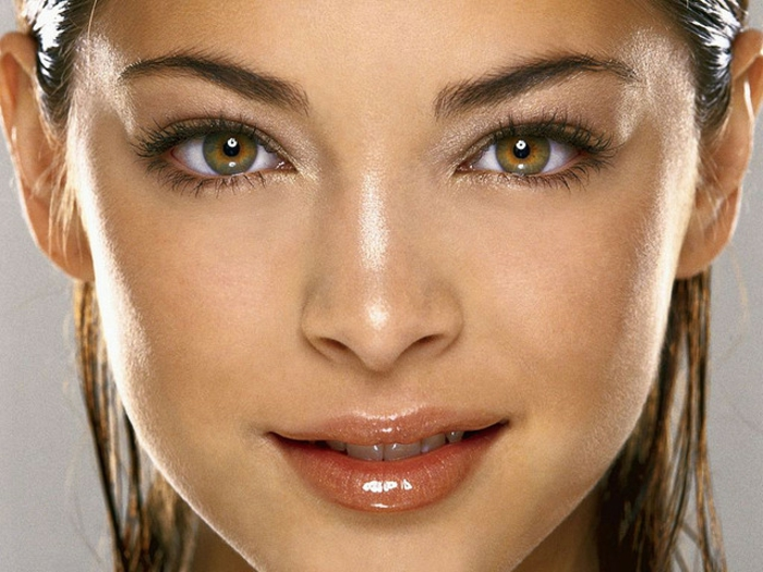hazel eyes, smiling woman with light brown and green eyes, delicate natural make up, shiny lip gloss, brown hair slicked back