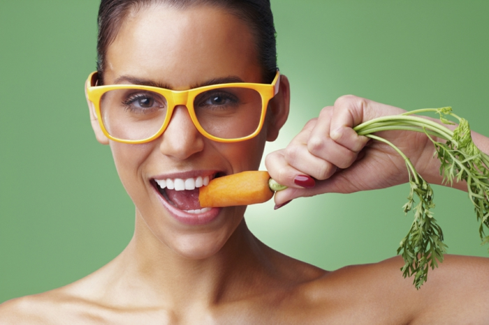 hazel eye color, smiling woman with big white teeth, brown hair tied back, wearing big glasses with yellow frames, holding and biting onto a carrot