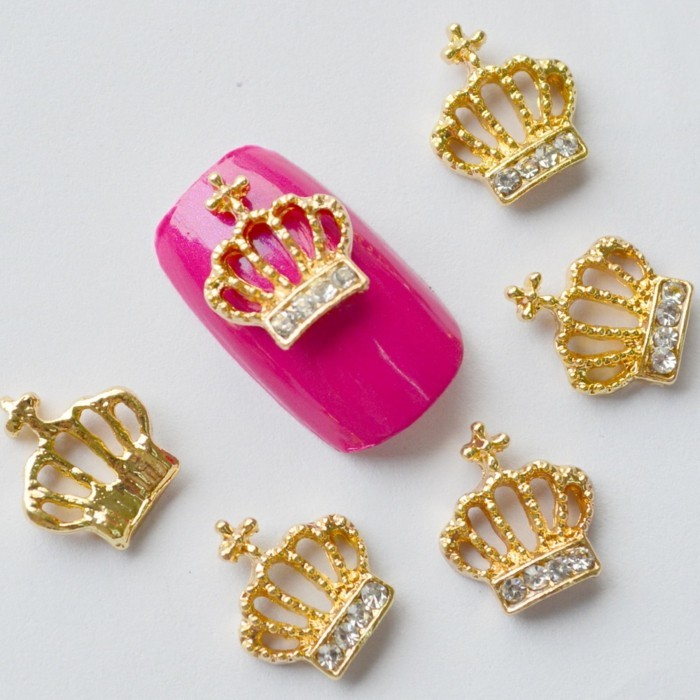 bling nail designs, hot pink fake nail, decorated with golden crown with rhinestones, next to several more crown decorations