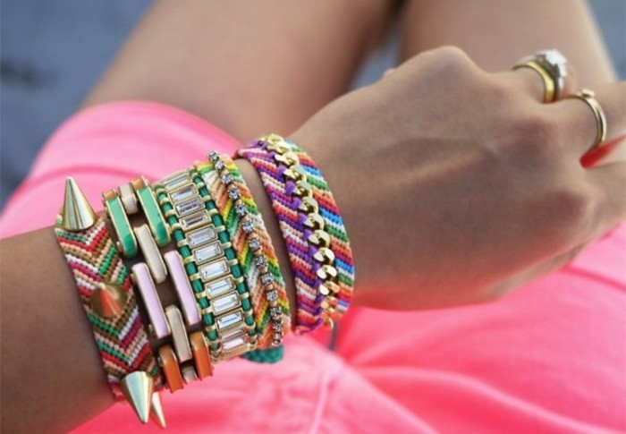 best friend birthday gifts, female hand decorated with many colorful bracelets, woven friendship bracelets, chain link bangles and two rings