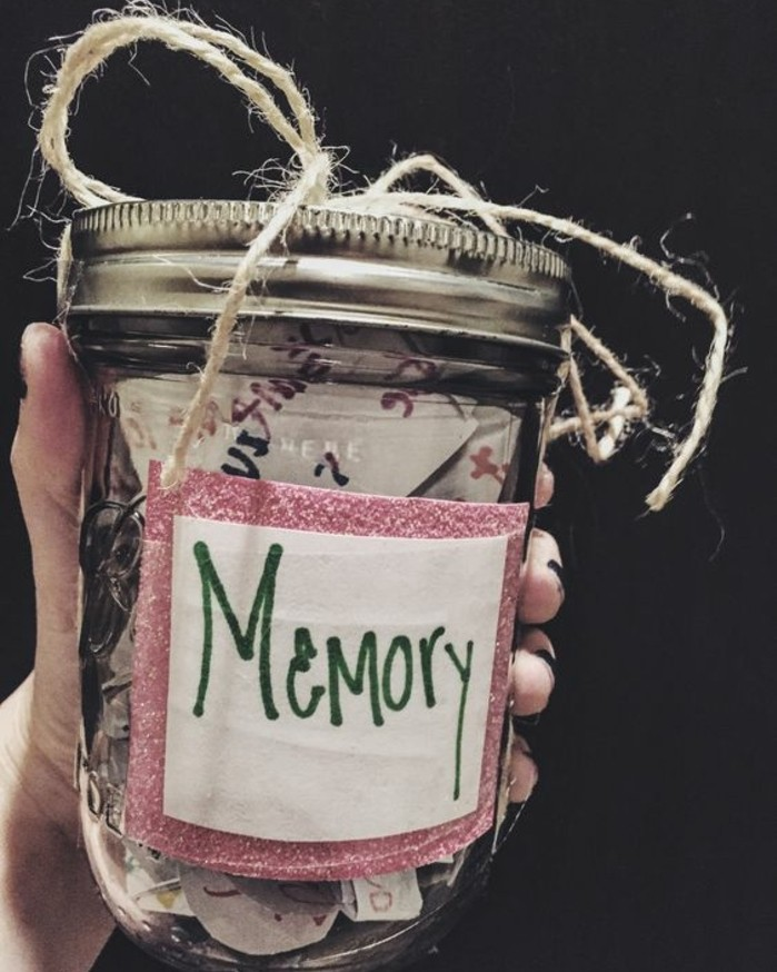 hand holding a clear mason jar, with silver lid, filled with colorful bits of paper, tied with simple string, with a white and pink label saying memory in green