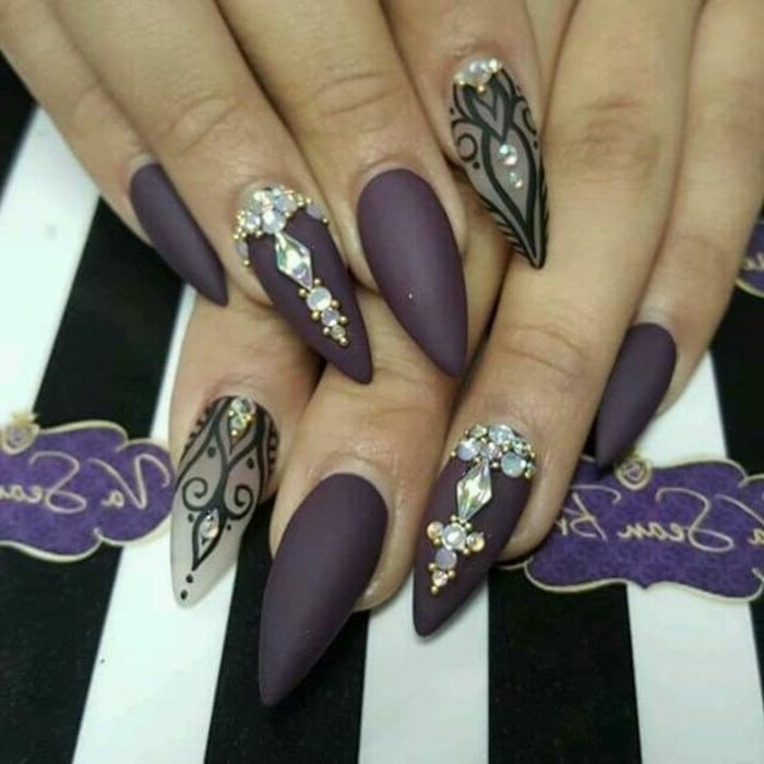 two hands with very sharp nails, painted in dark purple polish, two nails kept clear and decorated with black drawings, another two decorated with rhinestones