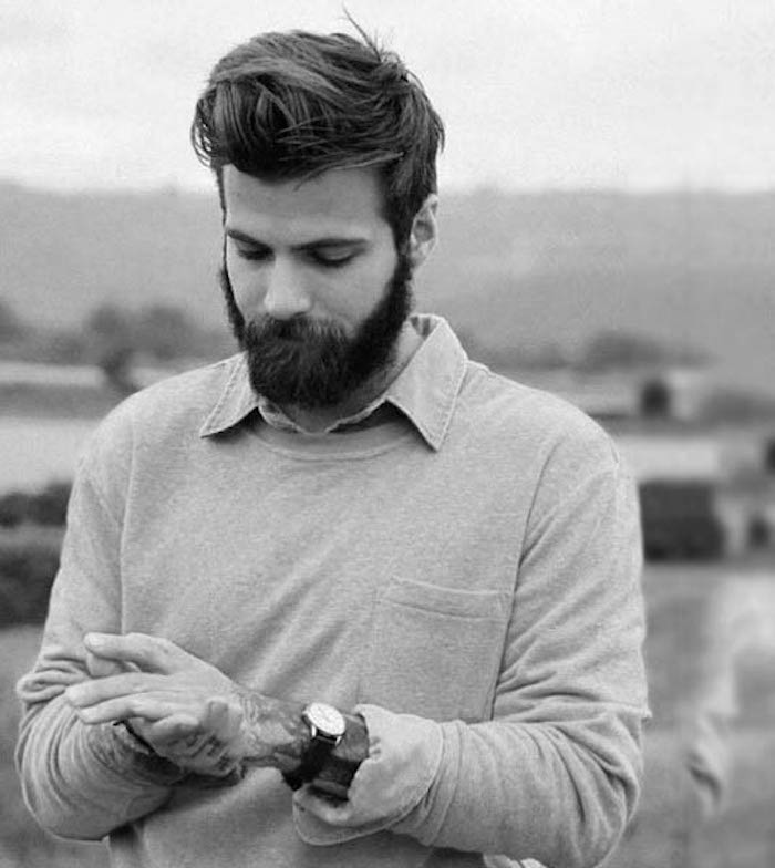 medium length hair, bearded man looking down, gelled-up messy hair in pompadour style, arm tattoos and watch