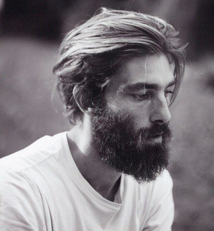 mid length hair, thoughtful man with big beard and white t-shirt, swept back hair with one lose strand