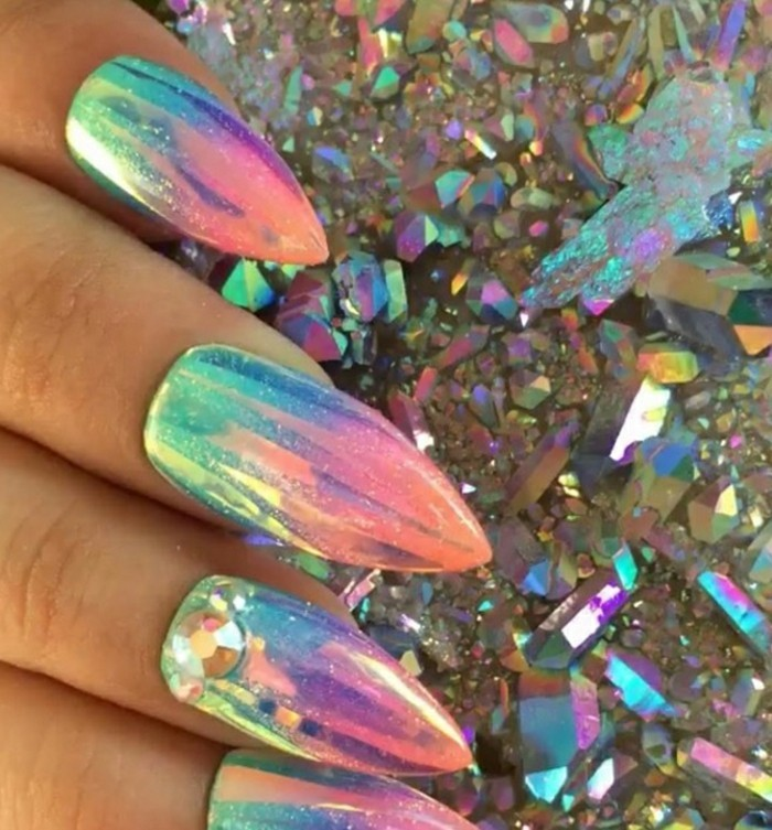 sharp mermaid nails, painted in iridescent nail polish and decorated with rhinestones