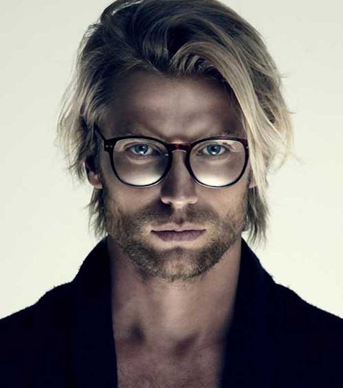shoulder length haircuts, blond man with layered messy hair, wearing glasses and a dark jumper