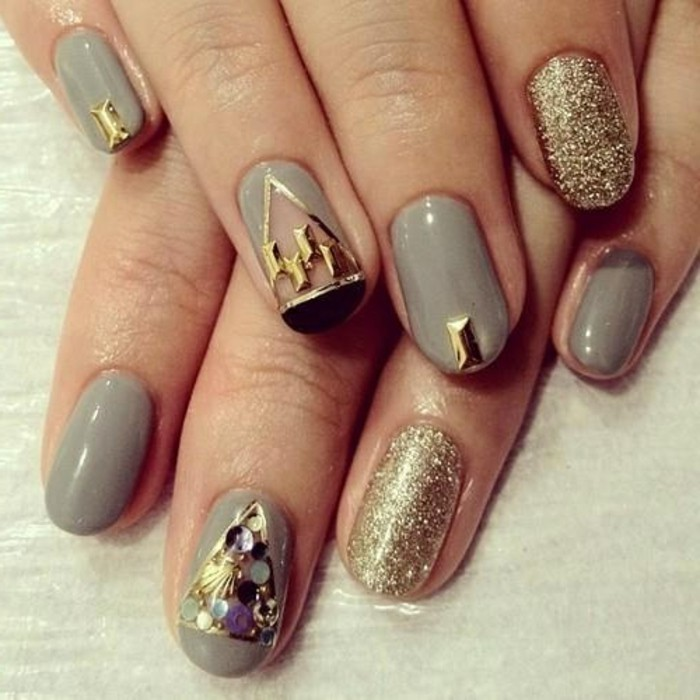 two hands with round nails, painted in grey and decorated with black gold details and/or covered in gold glitter
