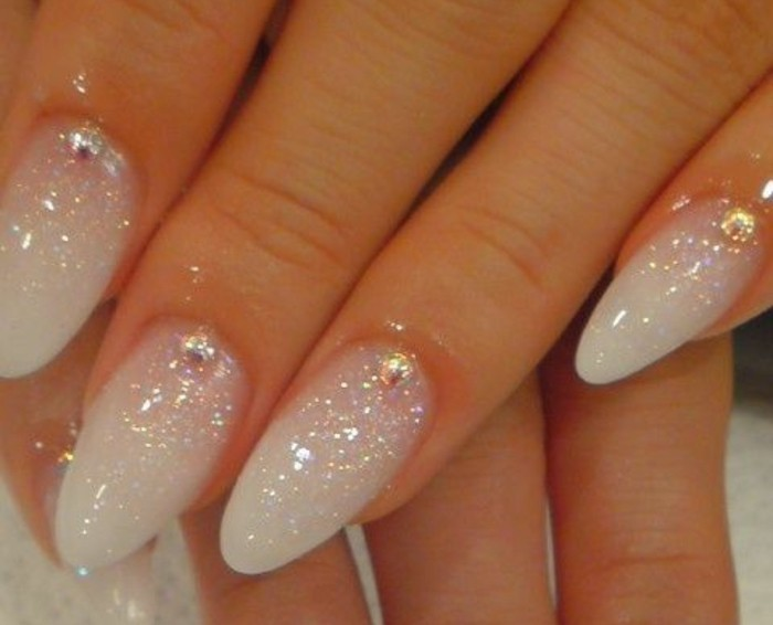 close up of four sharp nails, painted in white polish, and covered in light glitter, with one rhinestone each