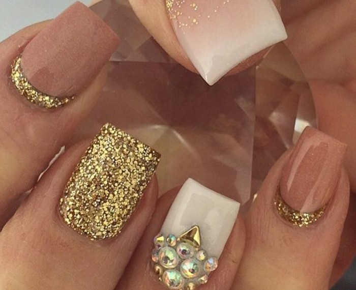 extreme close up of nails painted in white, dark nude and glittering gold, white nail decorated with pearl-shaped rhinestones