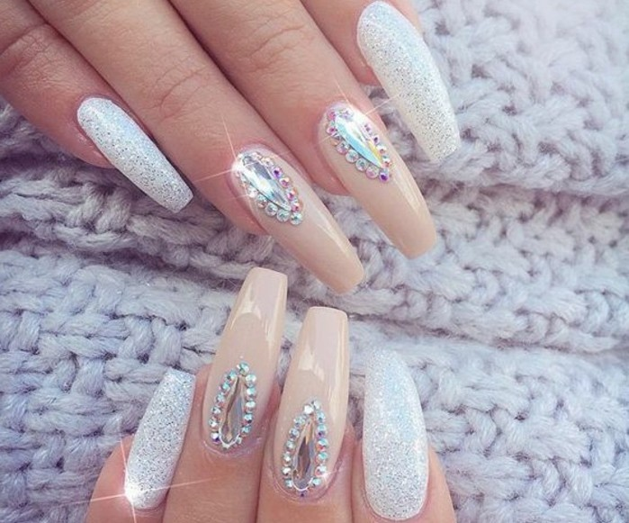 nude nails with rhinestones, eight long square nails, four with white polish and glitter, four with nude polish and rhinestones