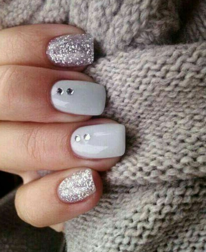 nail designs with rhinestones and glitter, close up of four fingers on grey woolen fabric, two nails have silver glitter polish, two are grey with rhinestone decoration