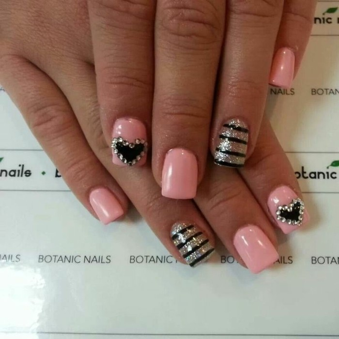 hand with square nails painted in pink, two nails decorated with black hearts and rhinestones, other two nails decorated with gold glitter and black stripes