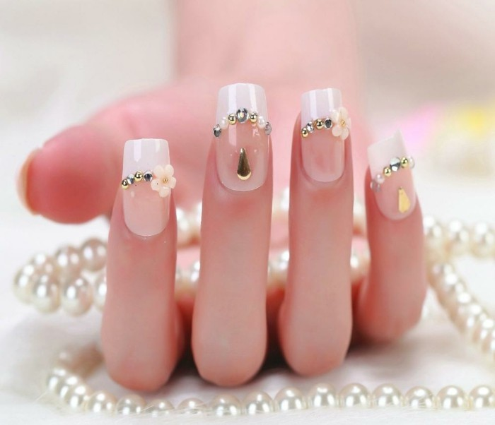 nail designs with rhinestones, hand with french manicure, decorated with silver and white rhinestones, golden teardrop-shaped stickers and acrylic flowers, holding pearl necklace