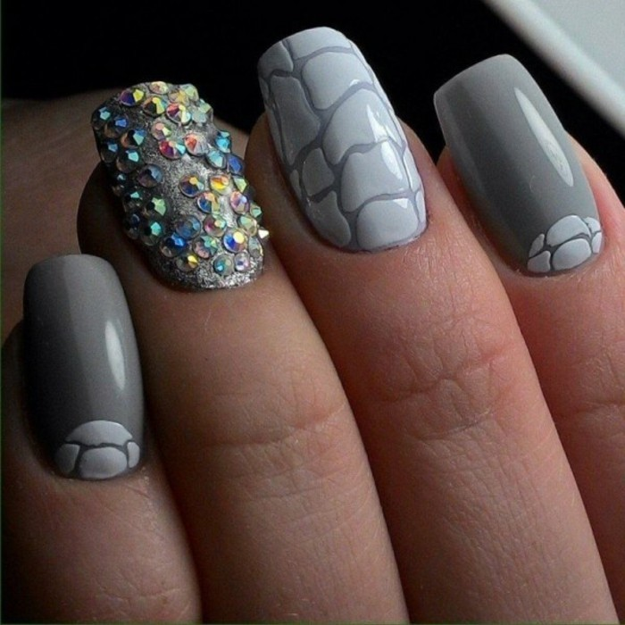 nail designs with rhinestones, close up of four nails, three dark grey with light grey details, one sparkling grey and decorated with many multicolored rhinestones