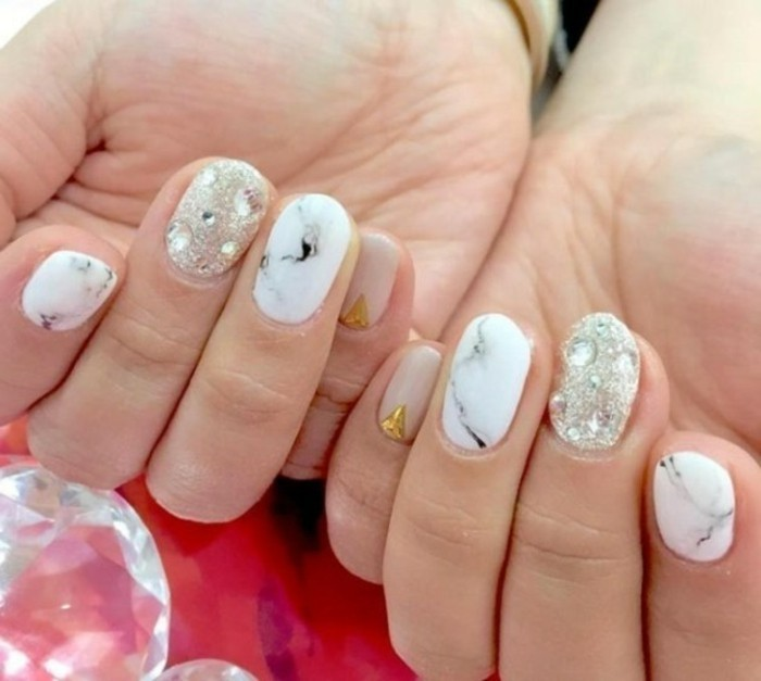 rhinestone nail art, two hands with differently colored nails, white and grey marble effect, pink with gold detail, glittering silver color with rhinestones