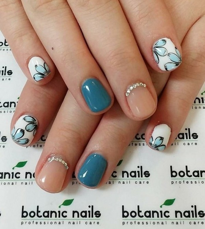 nails with rhinestones, two hands, one resting on top of another, nails in pastel pink with rhinestones and blue, pinkie and index finger nails white with pale blue flowers
