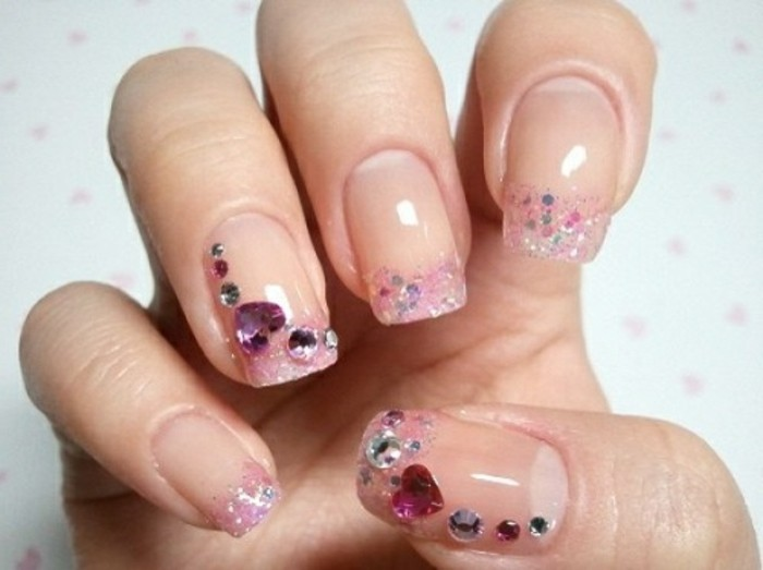 nails with rhinestones, close up of hand with square nails, pale shiny nail polish, pink glitter with round and heart-shaped stones