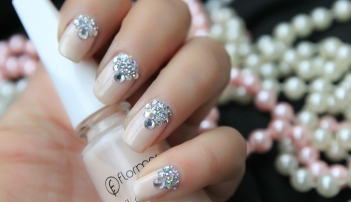 nails with rhinestones, hand holding a bottle of nude colored nail polish, nails painted in same color with rhinestone decorations